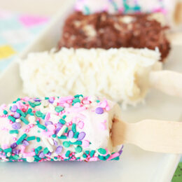 frozen banana pops on a white tray with different toppings: sprinkles, coconut, chocolate pieces