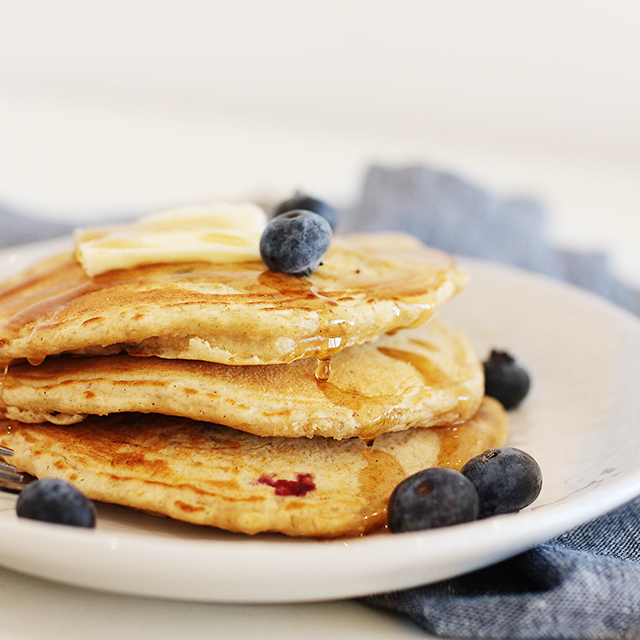 pancakes topped with butter, blueberries, and syrup on a white plate with a blue napkin
