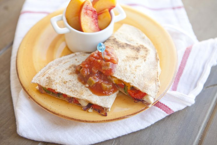 grilled quesadillas topped with salsa and served with peaches on a yellow plate