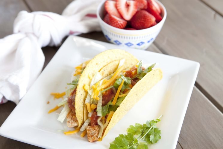 crunchy chicken tacos on a square plate served with strawberries