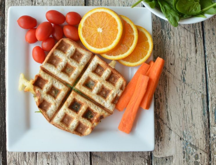 grilled cheese on a white square plate served with oranges, tomatoes and carrots