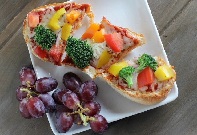 french bread pizza topped with tomatoes, broccoli and bell peppers and served with grapes
