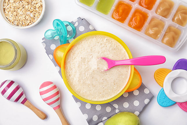 homemade baby food cereal from scratch in a yellow bowl with pink spoon and baby toys in the background