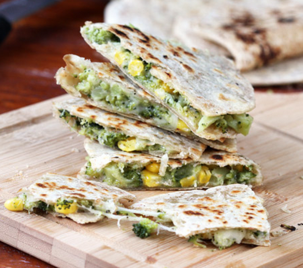 broccoli and cheese quesadillas stacked on a wooden cutting board