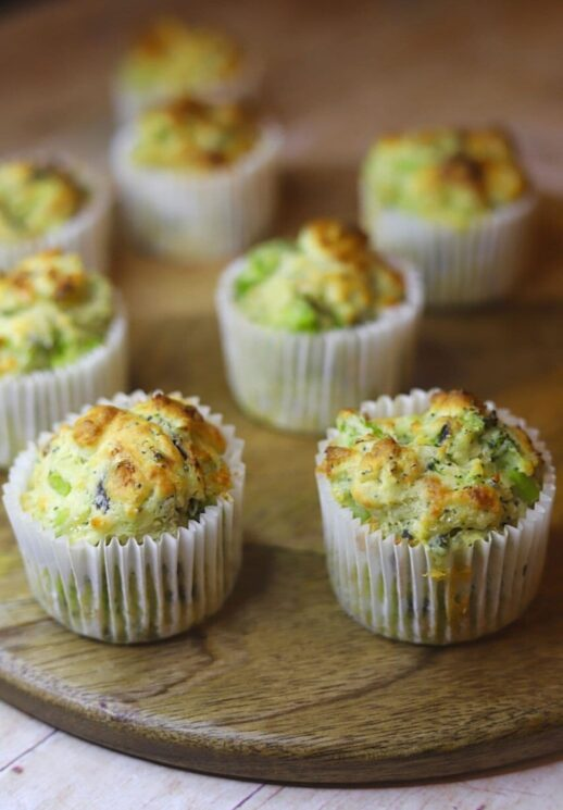 broccoli and cheese muffins in white paper liners on a wooden table