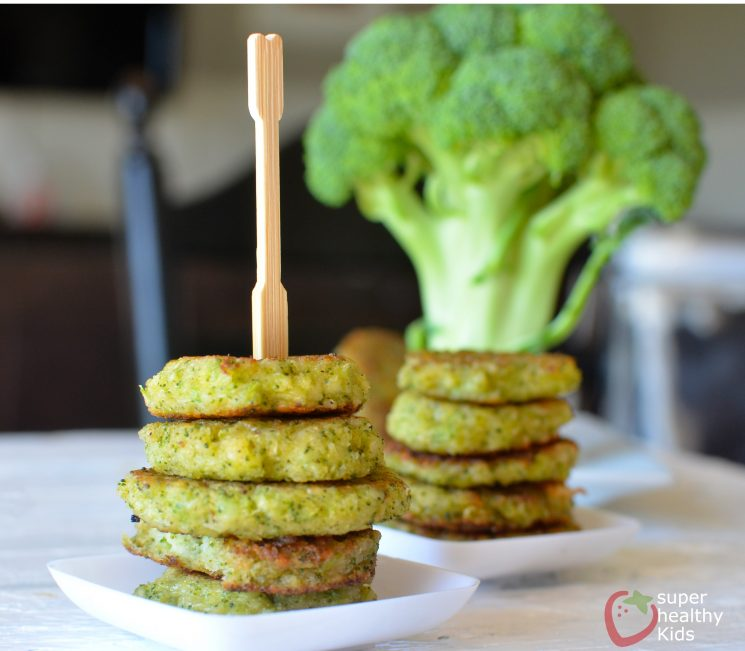 small stacks of cheesy broccoli fritters on small serving plates with a serving pick on top